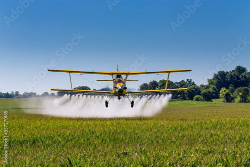 Fotografija Yellow Crop Duster Spraying Pestisides On Crops