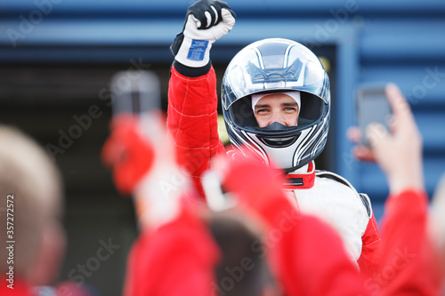 Fotografia Racer cheering with team on track