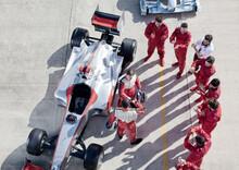 Team Surrounding Racer On Track