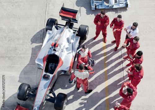 Fotografia Team surrounding racer on track