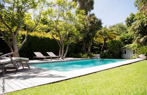 Lawn chairs and swimming pool in backyard Fototapeta