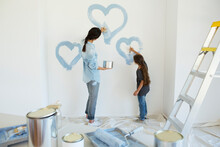 Mother And Daughter Painting Blue Hearts On Wall In New House