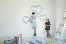 Mother And Daughter Painting Blue Hearts On Wall