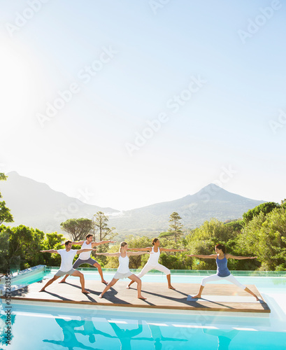 Photo People practicing yoga at poolside