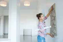 Woman Hanging Wallpaper In New...