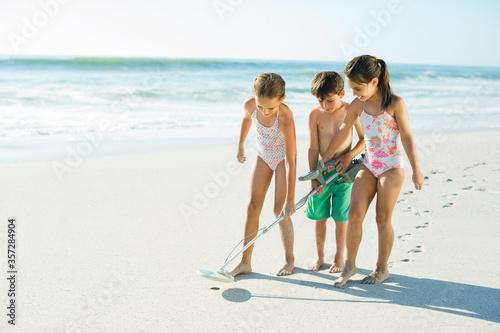 Obraz Children using metal detector on beach - fototapety do salonu