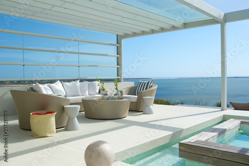 Photo Sofa and chairs by swimming pool overlooking ocean