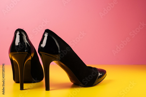Obraz Close up of stylish black high heels shoes on a yellow table with a pink background. - fototapety do salonu