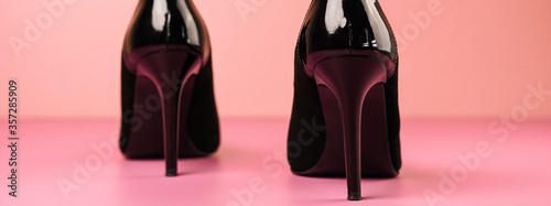 Obraz Close up of stylish black high heels shoes on a pink table with a light pink background. - fototapety do salonu