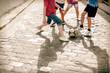 canvas print picture - Children playing with soccer ball on cobblestone street