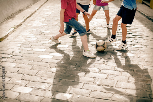 Fotomural Children playing with soccer ball on cobblestone street