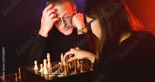 Photo Senior man plays a chess with a brunette woman in a dark studio