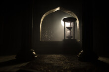 Silhouette Of Hourglass Inside Room. Abstract Surreal Idea With Empty Space. Selective Focus