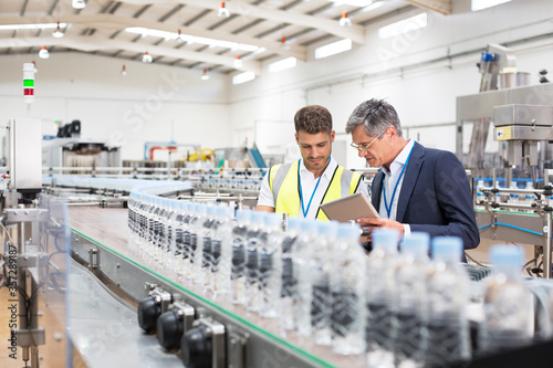 Cuadros en Lienzo Supervisor and manager watching plastic bottles on conveyor belt