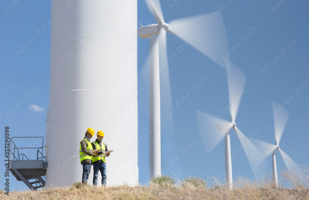 Fototapeta Workers talking by wind turbines in rural landscape