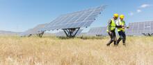 Workers Walking By Solar Panels In Rural Landscape