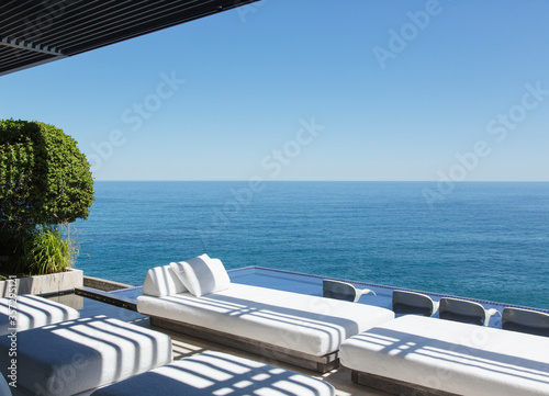 Sofas and infinity pool overlooking ocean Canvas Print