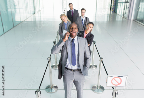 Photo Businessman talking on cell phone in line