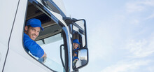 Portrait Of Smiling Truck Driver Leaning Out Window