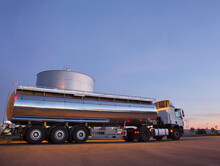 Stainless Steel Milk Tanker Next To Silage Storage Tower