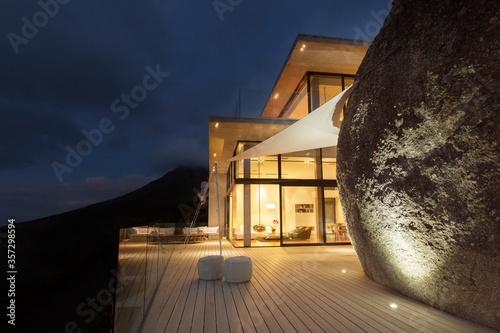 Valokuva Illuminated modern house with rock feature and balcony