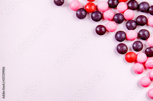 Light pink background with round pink and purple candys on the right side. Top view with copy space