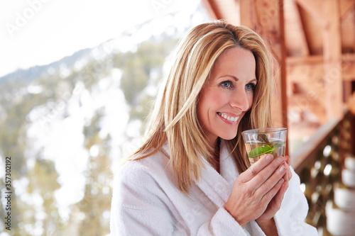 Fototapeta Woman having drink on cabin balcony