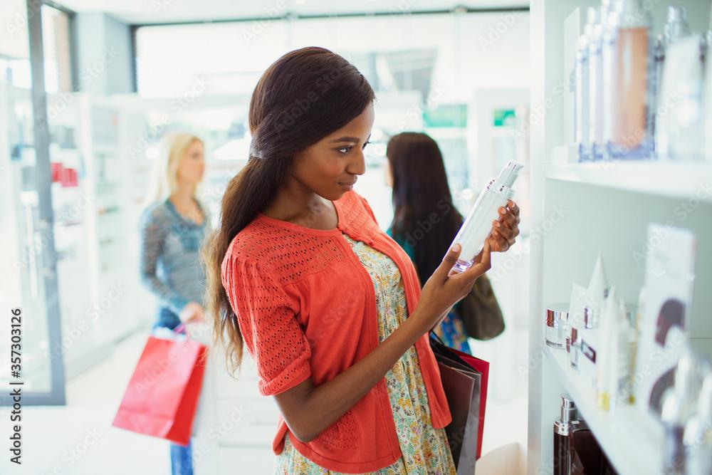 Fototapeta Woman examining skincare product in drugstore