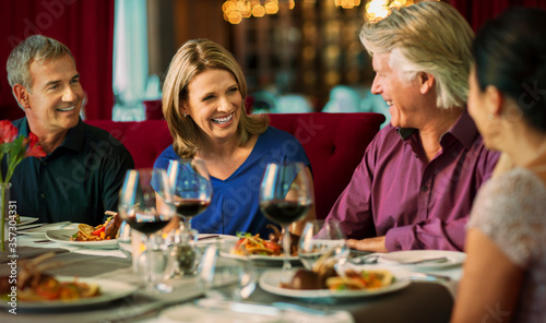 Tablou Canvas Smiling people enjoying their meal in restaurant