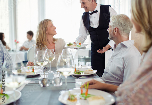 Waiter serving fancy dish to woman sitting at restaurant table Canvas Print