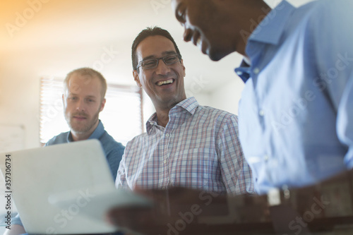 Foto Men using digital tablet and laptop in office