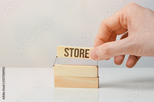 Fototapety, obrazy: Shop development concept - hand holds wooden block with the inscription.