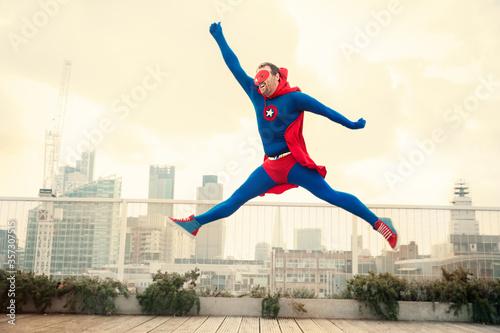 Superhero jumping on city rooftop Fototapeta