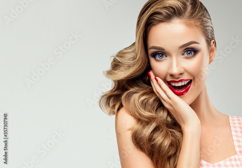 Woman surprise showing product .Beautiful girl  with smile pointing to the side . Presenting your product. Expressive facial expressions emotions