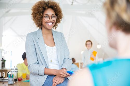 Portrait businesswoman in eyeglasses smart phone smiling in office Wallpaper Mural