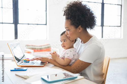 Fényképezés Mother working from home with daughter sitting on her lap