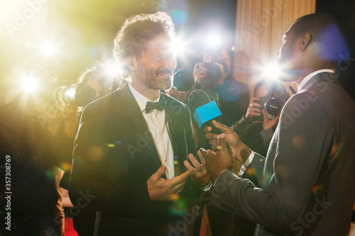 Fotomural Celebrity being interviewed and photographed by paparazzi at event