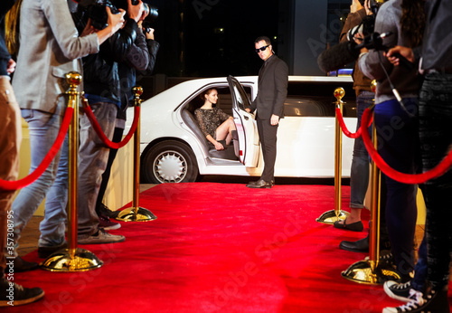 Photo Bodyguard opening limousine for celebrity arriving at red carpet event