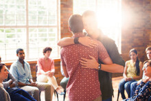 Men Hugging At Group Therapy Session