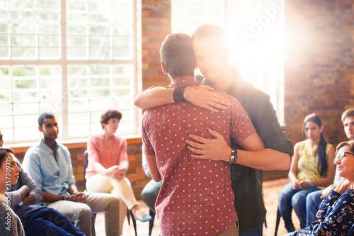 Obraz na plátně Men hugging at group therapy session