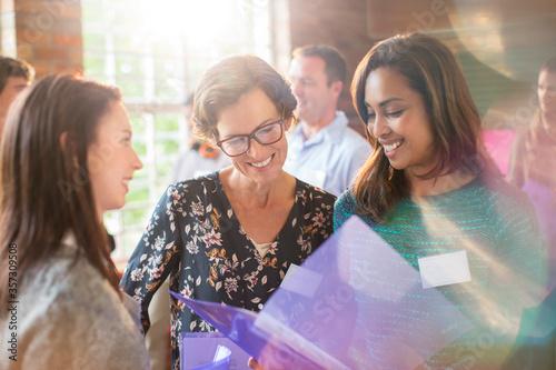 Smiling women looking at paperwork in community center Tapéta, Fotótapéta