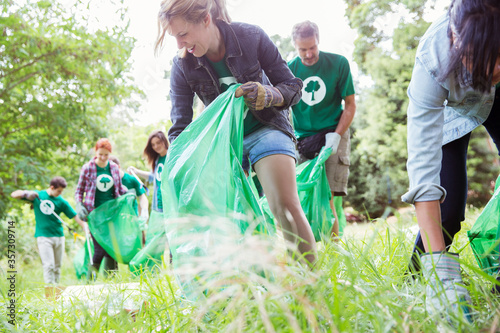Obraz na płótnie Environmentalist volunteers picking up trash in field