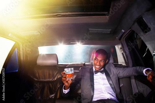 Obraz na plátně Celebrity drinking cocktail inside limousine outside event