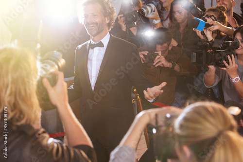 Fotomural Smiling celebrity posing for paparazzi photographers at event