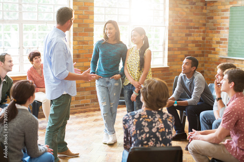 Photo Man and women talking in group therapy session