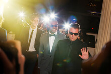 Bodyguard Escorting Celebrities Arriving At Event Being Photographed By Paparazzi