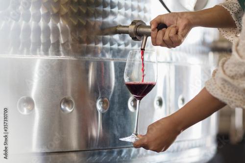 Fototapeta Vintner barrel tasting red wine from stainless steel vat obraz