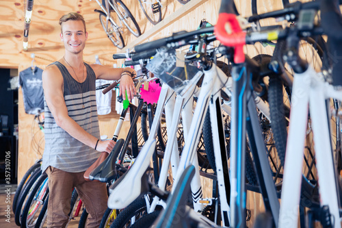 Fotografía Portrait smiling young man leaning on rack in bicycle shop