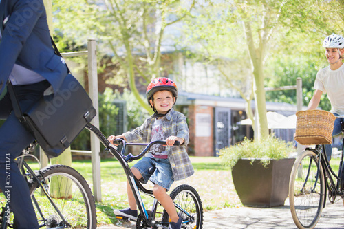 Fototapeta Portrait smiling boy in helmet riding tandem bicycle father in park