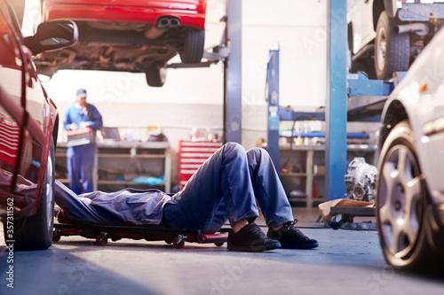Fototapeta Mechanic under car in auto repair shop obraz